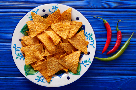 Nachos chips and chili peppers on mexican plate over blue wooden table