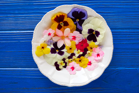 Edible flowers salad in a plate on blue wooden table Stok Fotoğraf - 74799669