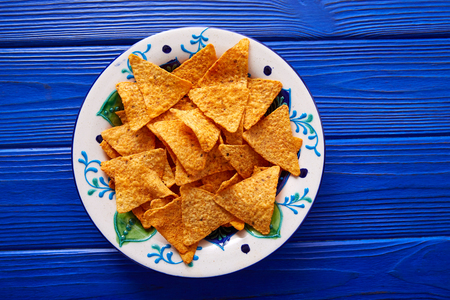 Nachos chips on mexican plate over blue wooden table