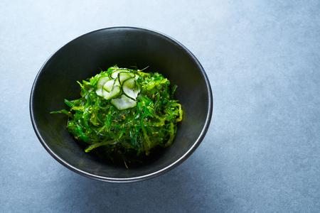 edible: Algae salad with cucumber sesame and soya in black bowl