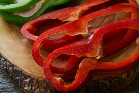 Green and red pepper slices on a cutting board of olive tree wood
