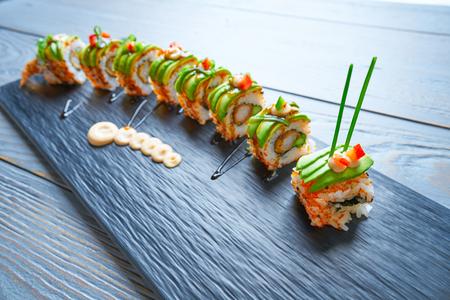 Dragon shape Sushi rice roll with nori prawn avocado sesame and teriyaki Фото со стока