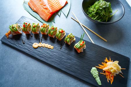 Dragon shape Sushi rice roll with nori prawn avocado sesame and teriyaki Stock Photo