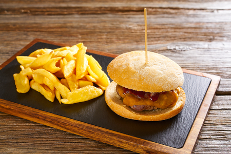 Burguer and french fries potato chips on wood table
