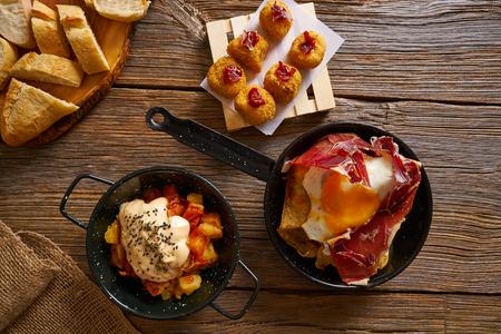 Tapas of Spain broken eggs Croquettes and Bravas potatoes Stock fotó