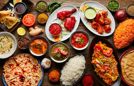 様々 な木製のテーブルにご飯とスパイスが香るインドのレシピ料理の盛り合わせ
