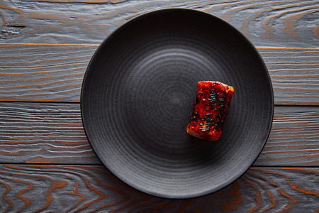 Grilled smoked eel on black plate modern cuisine gastronomy