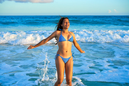 Latin beautiful bikini girl happy jumping in Caribbean beach sunset
