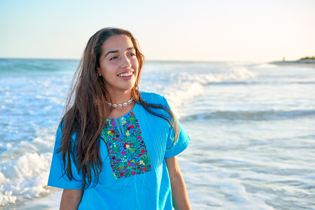 Latin beautiful girl in Caribbean beach sunset with embroidery dress Stock Photo