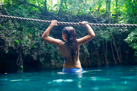 woman bath: Girl playing with rope in Cenote sinkhole in  Riviera Maya at mayan Mexico