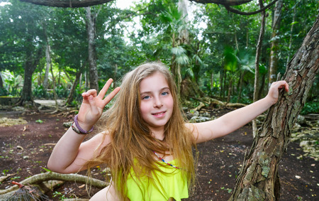 Caucasian girl playing victory sign in the rainforest jungle