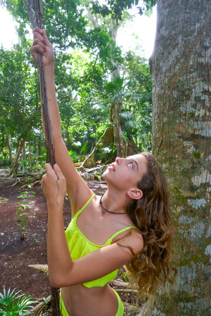 Caucasian girl playing with lianas in the rainforest jungle