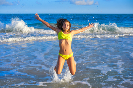 Bikini teen girl jumping happyt in Caribbean sunset beach splashing shore Foto de archivo