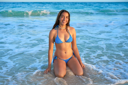 Latin beautiful bikini girl happy sitting in Caribbean beach sunset