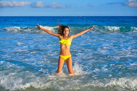Bikini teen girl jumping happyt in Caribbean sunset beach splashing shore Standard-Bild