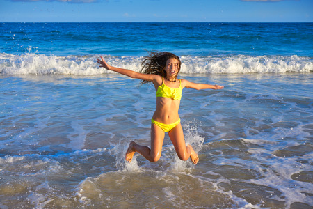 Bikini teen girl jumping happyt in Caribbean sunset beach splashing shore Archivio Fotografico