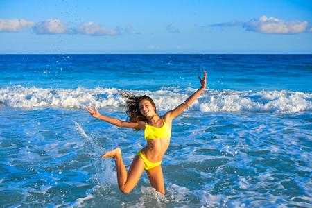 Bikini teen girl jumping happyt in Caribbean sunset beach splashing shore Reklamní fotografie