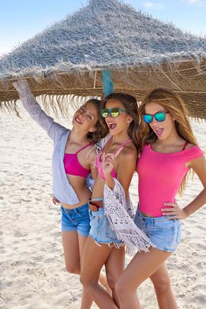 teen best friends girls under thatch umbrella having fun on a beach