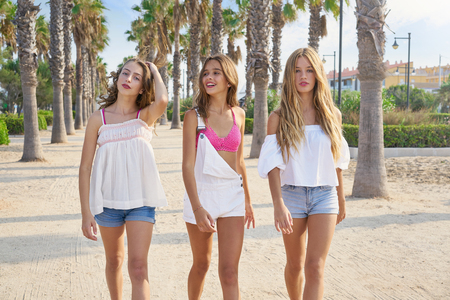 Teen best friends girls group walking happy in a palm trees beach area Archivio Fotografico