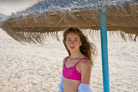 teen girl under thatch umbrella on a beach portrait with bikini top