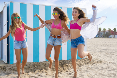 Best friends teen girls group running happy in a beach having fun