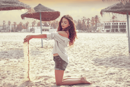 Teen girl on the beach playing with sand near thatch umbrellas filtered image Stock Photo