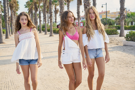 Teen best friends girls group walking happy in a palm trees beach area Foto de archivo