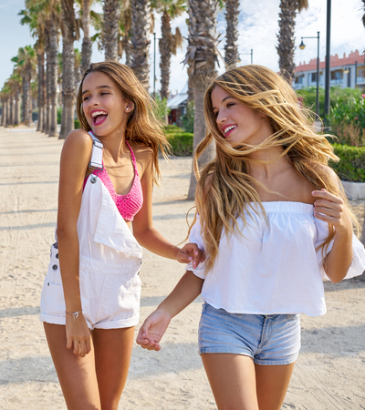 Teen best friends girls walking happy in a palm trees beach area Foto de archivo