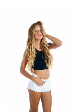 Blond teenager girl touching hair on white background