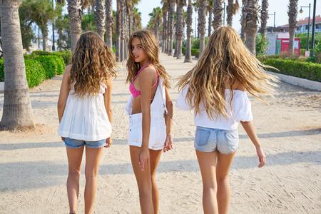 Teen best friends girls group walking happy in a palm trees beach area Foto de archivo