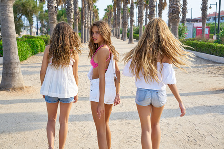 Teen best friends girls group walking happy in a palm trees beach area Stock fotó