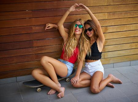 Best friends teen girls on skate heart shape hands fingers smiling having fun