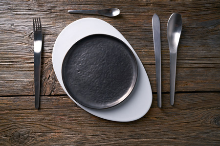 Modern cuisine plate table service with cutlery o aged wooden board Banque d'images