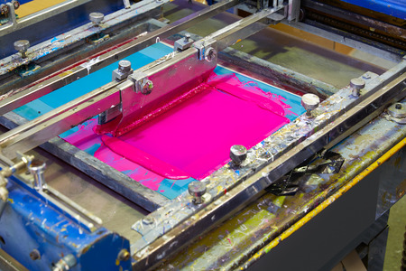 Serigraphy Printer ink machine pink magenta color in printing factory Stock Photo