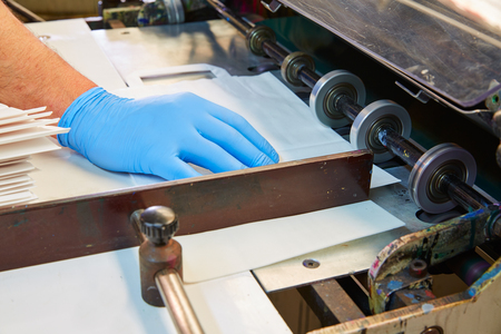 Flexo printing machine in a print factory operator hand detail