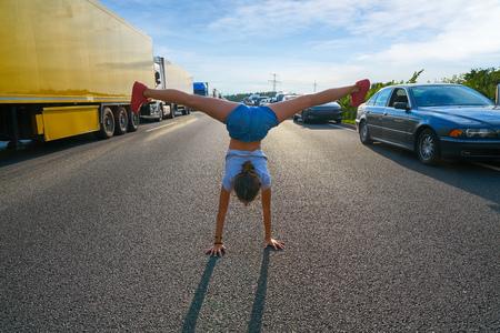 Ragazza acrobatica stand mano in una strada di ingorgo divertendosi Archivio Fotografico