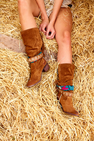 female legs with leather brown boots relaxed on straw bale barn Stock Photo