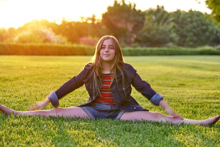 Blond kid girl splitting legs at sunset park outdoor