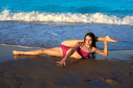 Acrobatic gymnastics bikini girl in a beach blue shore at summer