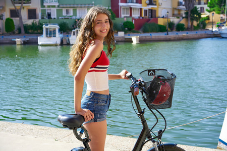 Girl riding a bike smiling in a Mediterranean port