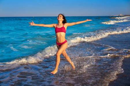 Bikini girl running to the beach shore water of Mediterranean sea Archivio Fotografico