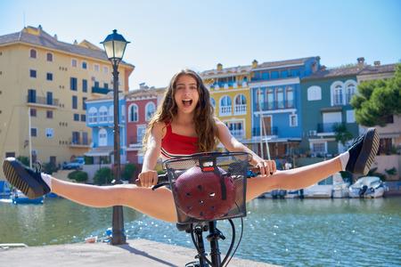 Acrobatic girl riding a bike in a Mediterranean marina port open split legs 免版税图像