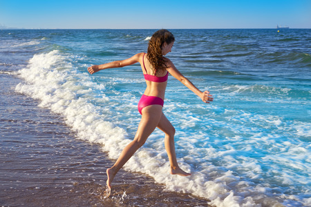 Bikini girl running to the beach shore water of Mediterranean sea 免版税图像