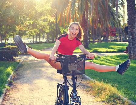 Acrobatic girl riding e-bike in a city park with red t-shirt foldable ebike Stock Photo