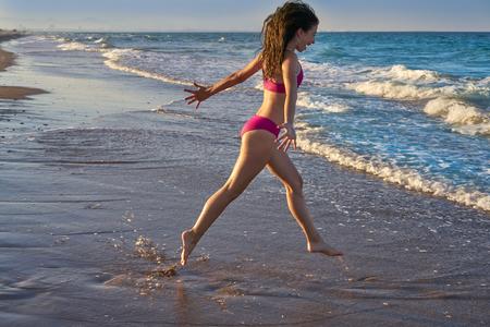 Bikini girl running to the beach shore water of Mediterranean sea Stock Photo