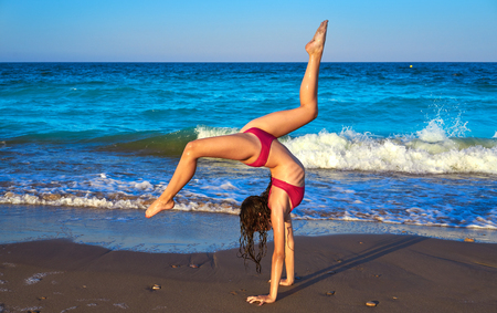 acrobatic gymnastics bikini girl in a beach blue shore at summer Stock Photo