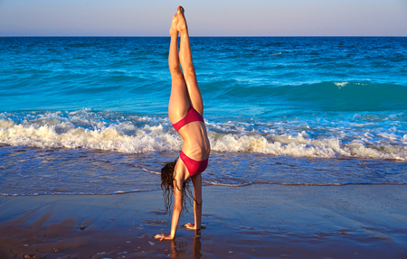 acrobatic gymnastics bikini girl in a beach blue shore at summer 免版税图像