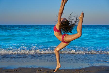 acrobatic gymnastics bikini girl in a beach blue shore at summer Stock Photo