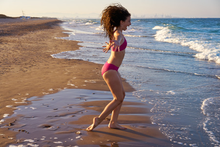Bikini girl running to the beach shore water of Mediterranean sea Banque d'images