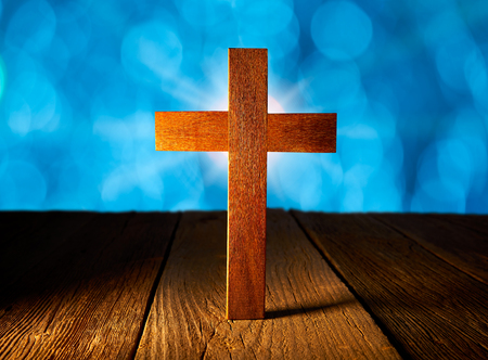 Christian wood cross on blue flare lights and wooden made background Imagens